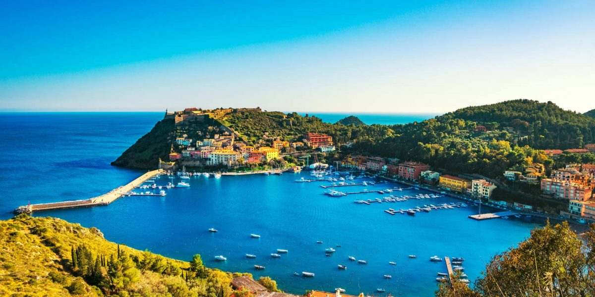Porto Ercole village and boats in harbor in a sea bay. Aerial view. Monte Argentario, Maremma Grosseto Tuscany, Italy